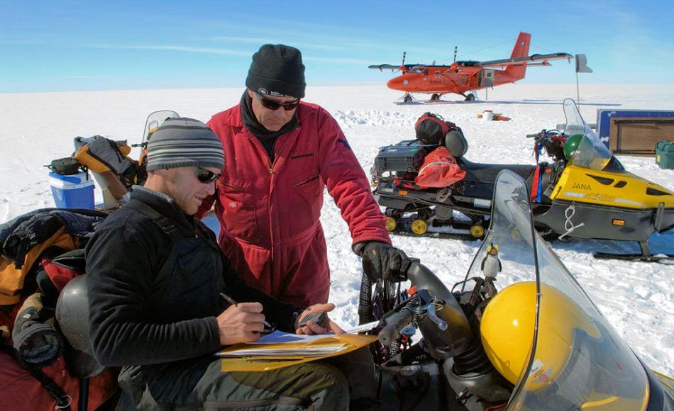 Ein Feldteam von Forschern auf dem Larsen C Eisschelf mit dem Flugzeug im Hintergrund. Durch den drohenden Abbruch konnte kein Camp auf dem Schelf aufgestellt werden. Bild: Peter Bucktrout, BAS