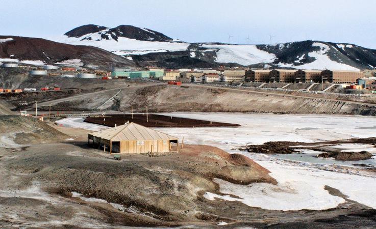 Die Discovery-Hütte auf Ross Island und im Hintergrund die US-amerikanische Basis McMurdo. Von